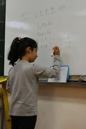 élève ecrivant son calcul au tableau